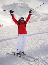 Skier raises hands in air triumphantly.