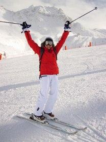 Skier raises hands in air triumphantly.
