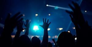 Hands raised in blue light.