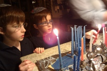 Two boys stand in front of Hanukkah candles.