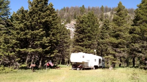 Travel trailer in the midst of mountains.