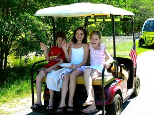 Three children sit on a golf cart. A boy and a girl wave hello.