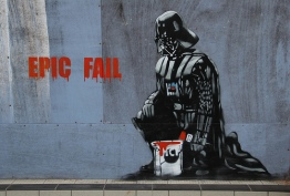 Darth Vader kneels on ground. He has painted the words Epic Fail on the wall.