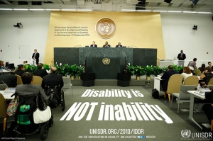 Room with people in meeting. Floor reads Disability is NOT inability.