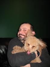 Man hugs a poodle.