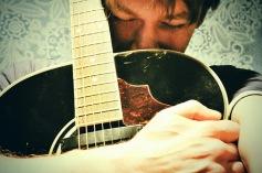 Man hugs guitar tightly.