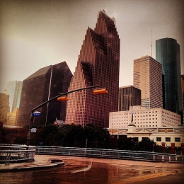 Picture of Houston skyline showing highway and tiered and glass skyscrapers.