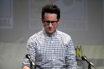 J.J. Abrams standing a podium next to microphone.