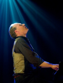Man has light shining down on him while he performs on stage.