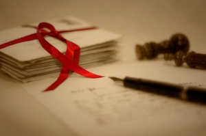 Love letters tied with red ribbon and one letter with pen.