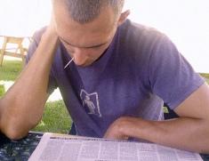 Man reads newspaper intently.