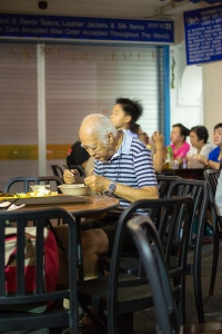 Chinese man eats food at table alone in restaurant.