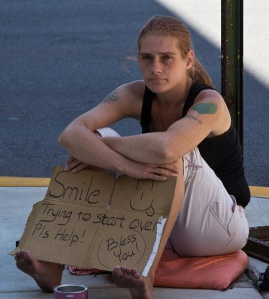 "Woman holds cardboard sign that reads, ""Smile! Smiley face. Trying to start over. Pls help! Bless you!"""
