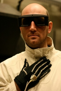 Man wearing glasses for virtual reality visual experience and gloves to monitor his heart.