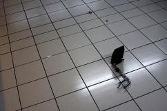 Wheelchair foot rest is alone on floor, broken off the wheelchair.