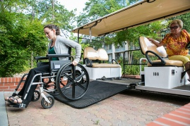 Woman uses portable ramp to lower her wheelchair.