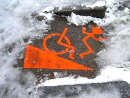 Wheelchair symbol on street with snow depicts person being thrown from wheelchair.
