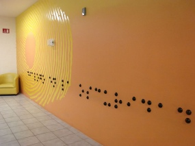 Large Braille makes a line across a full wall with some round tactile elements on the wall as well.