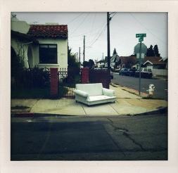 Large sofa sits on a sidwalk next to the curb cut