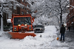 Snow plow shovels snow near man shoveling snow off sidewalk.