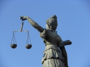 Statue of woman holding scales representing weighing the sides of justice.