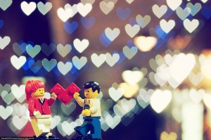 A lego man and lego woman share a lego heart with hearts in the background.