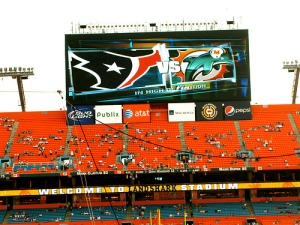Houston Texans and Miami Dolphins helmets on display in a football stadium.
