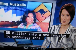 Captions on bottom of TV screen showing news about Oprah and Australia.