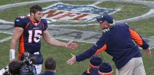 Tim Tebow in quarterback uniform, number 15 for the Denver Broncos on the playing field.