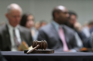 Gavel rests on top of desk with court room participants in distance