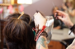 Person gets hair cut by a person with tattoed arm and hair clips with scissors in their hands.
