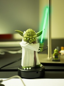 Soft green room with Yoda with lightsaber lit green on a desk.