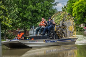 Airboat travels on water over a city street.