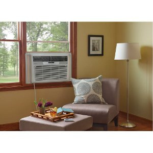 Room with chair immediately next to a window air conditioning unit.
