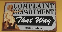 Sign shows little girl pointing away and says: Complaint Department that way 200 miles.