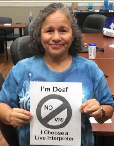 Woman holds up sign that says I'm Deaf, No VRI