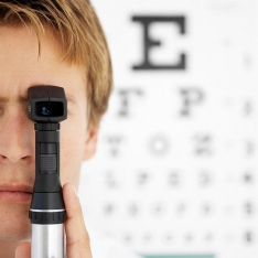 Boy testing eye sight in front of eye chart.