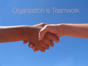 Two people shake hands and words above say, Organization is Teamwork.