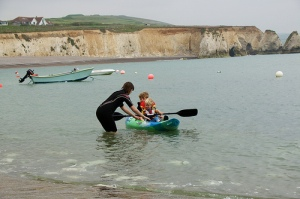 Woman wearing wetsuit assists child in ocean kayak in front of English Channel white cliffs.