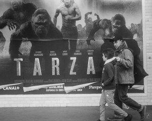 Sign of Tarzan and King Kong with father and son walking in front of it.