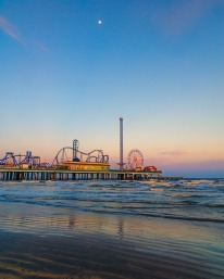 Galveston's Pleasure Pier has a Ferris Wheel and rides on a pier over the Gulf of Mexico waters.