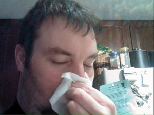 Man blows nose into a tissue.