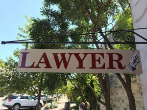 Sign says Lawyer and points to a business.