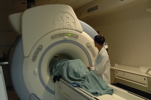 Person under sheet having MRI medical test with medical personnel watching.