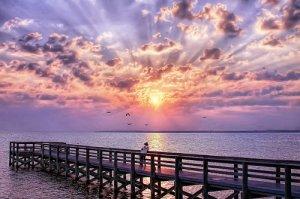 Sunrise or sunset over a bridge.