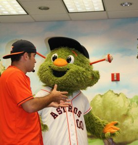 Young man in Astros fan clothes speaks with the Houston Astros furry green mascot, Orbit.