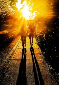 Sun shines brightly on a couple walking down the street holding hands.