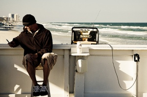 Man is dressed in jacket and cap, working with cell phone and laptop is plugged into a wall on the boardwalk in front of the ocean.