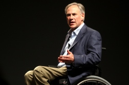 Governor Greg Abbott is speaking, the top rim of his wheelchair is visible.