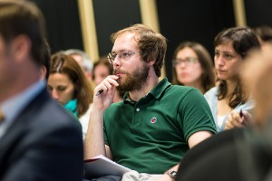 Man in green shirt sits among and audience with hand to chin in deep thought.